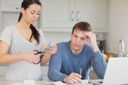 Two people working on finances and cut through the credit card photo