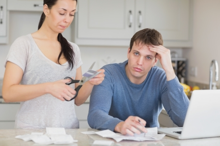 Disappointed woman cutting through a credit card with stressed husband in kitchen photo