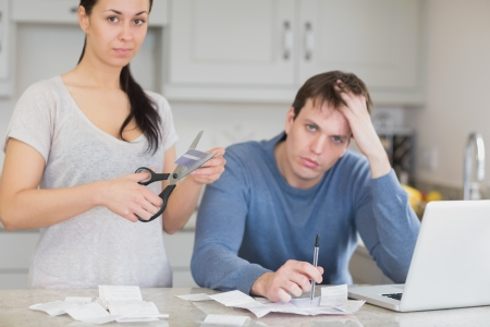 Disappointed couple in the kitchen cutting credit card and looking at finances on laptop photo