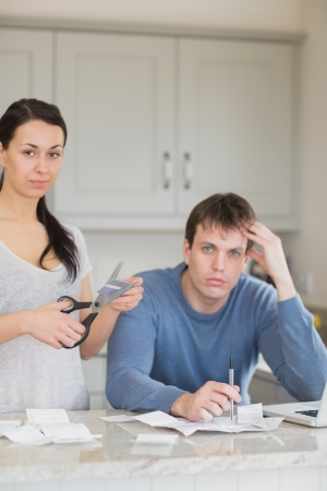 Woman cutting up credit card with man calculating finances with laptop photo