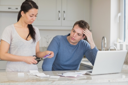 Wife cutting up credit card with husband watching in kitchen with laptop photo