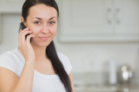 Young woman calling with the mobile phone while standing in the kitchen photo