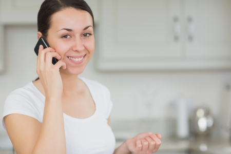 Young woman standing in the kitchen while calling with the mobile phone photo
