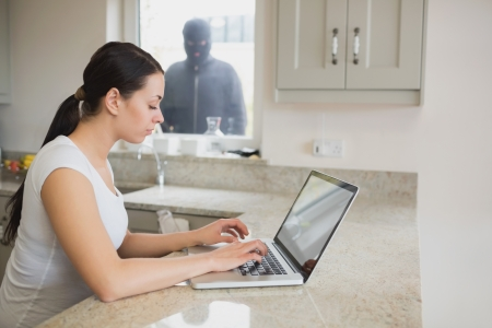 unknowing: Woman using a laptop in the kitchen with burglar standing at the window