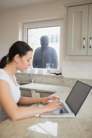 Young woman using her laptop and is observed by a robber at the window photo