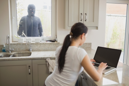 unknowing: Woman on laptop in kitchen being observed by burglar through window Stock Photo