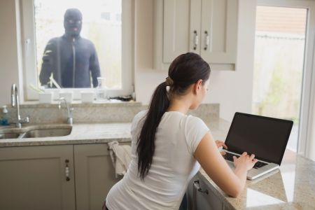Robber looking at woman in kitchen using laptop through window photo