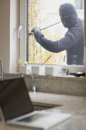 opening window: Ladr�n abrir ventana con barra de hierro para obtener computadora port�til en encimera de la cocina