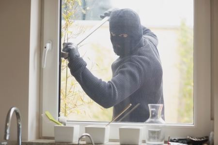 Burglar breaking a kitchen window with a crobar from outside photo