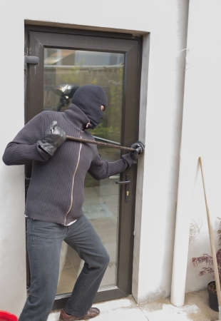 Burglar breaking door from outside with crow bar photo