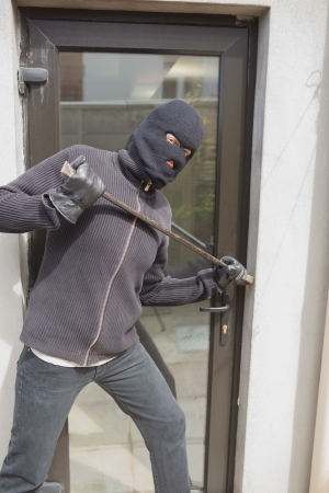 Burglar breaking into home using crow bar through back door photo