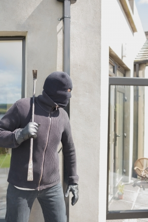 thievery: Robber hiding behind a wall with crow bar Stock Photo