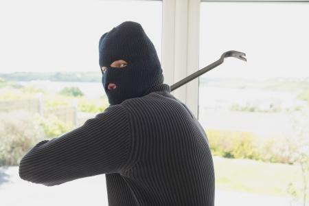 intruding: Burgalr swinging crow bar in home