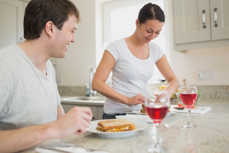 Two young people having lunch and drinking wine in the kitchen photo