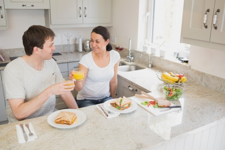 Two young people sitting in the kitchen and having a healthy meal photo