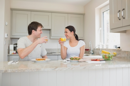 Young people drinking orange juice and eating sandwiches in the kitchen photo