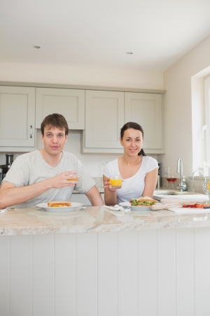 Two friends eating sandwiches and drinking juice in the kitchen photo