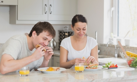 Two people eating sandwiches and drinking juice while sitting in the kitchen Stock Photo - 16053371