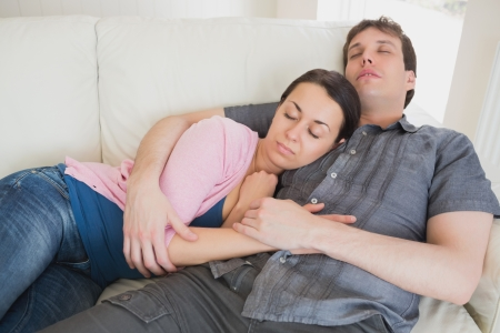 Young couple sleeping on the couch in the living room photo