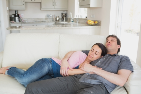 Two people lying on the couch in the living room while sleeping photo