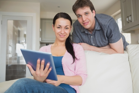 Woman sitting on the couch with a man behind her while using the tablet computer photo