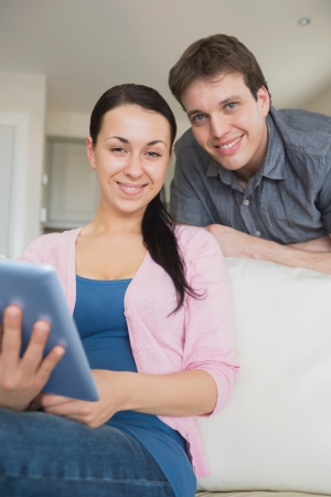 Young couple using a tablet computer and having fun on the couch photo