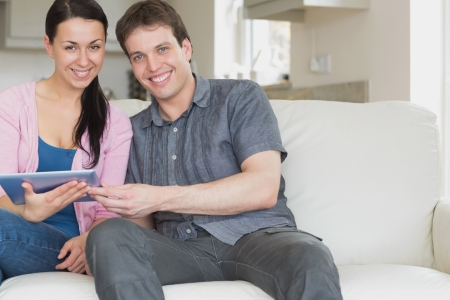 Young couple sitting on the couch and having fun while using the tablet computer photo