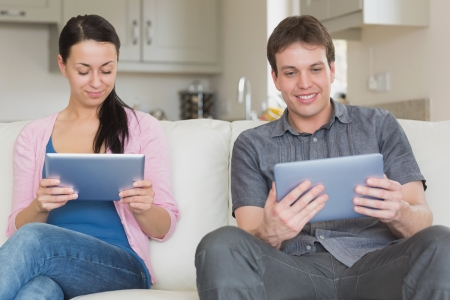 Young couple sitting on the couch while using a tablet laptop photo