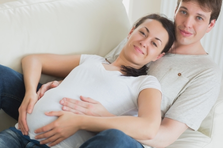 Pregant woman and husband lying on couch toucher her belly photo