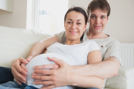 Couple expecting a newborn lying on the couch and relaxing photo