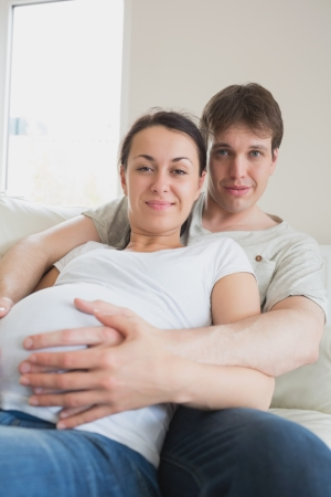 Pregnant woman lying on couch with partner in living room photo