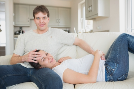 Prospective parents enjoying their spare time while lying on the couch photo