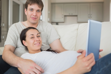 Young prospective parents lying on the couch while using the ebook and relaxing photo