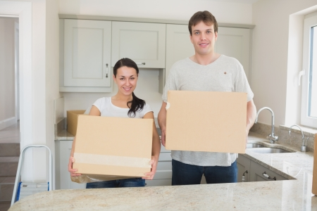 Young man and woman holding moving boxes in kitchen photo