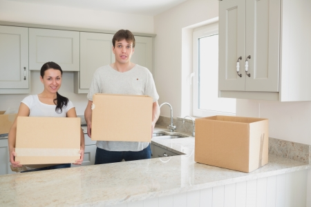 Young couple standing in the kitchen while holding boxes for a relocation photo