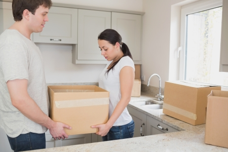 Young couple in the kitchen holding a box for a relocation Stock Photo - 16054117
