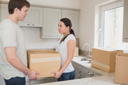 Young couple standing in the kitchen while holding a box for a relocation photo