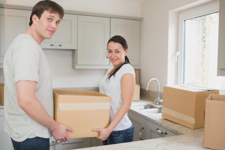 Young couple in the kitchen holding moving boxes and smiling photo