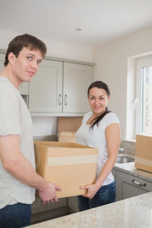 Young relocating couple standing in the kitchen while holding a box photo