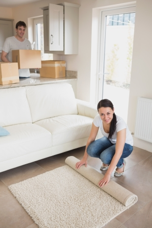 Two people furnishing the house while holding boxes and rolling out a carpet Stock Photo - 16054289