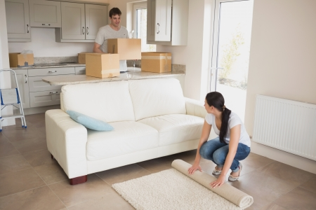 Two young people moving into their house and furnishing the living room photo
