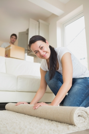 Two young people moving into the house and furnishing the living room photo