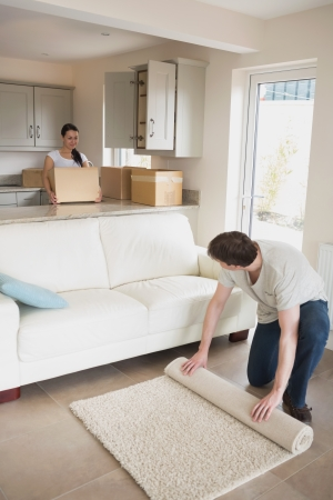 Two young people furnishing the kitchen and living room for a relocation photo