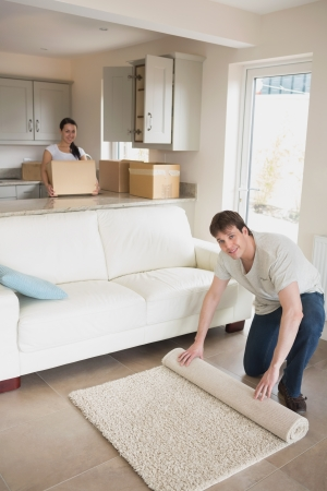 Young man and woman furnishing their kitchen and living room for a relocation photo