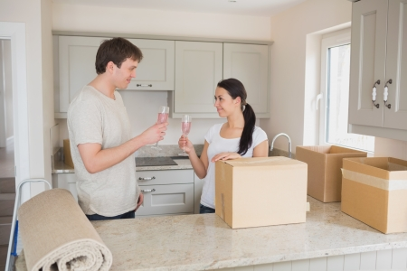 Two young people celebrating move into new home with champagne in kitchen photo