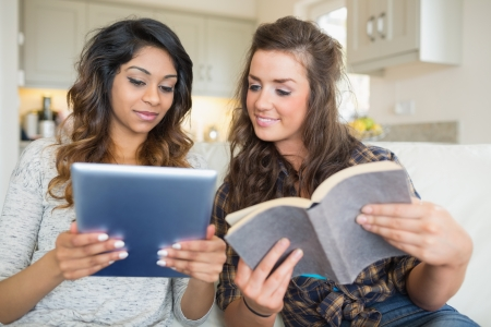 amity: Two girls reading a book and holding a tablet computer while sitting in a couch