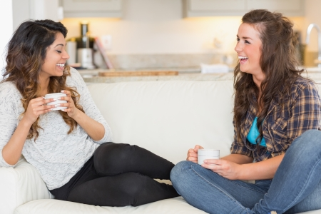 Two girls having coffee and laughing on sofa Stock Photo - 16076634