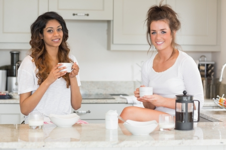 Two smiling friends having coffee in kitchen photo