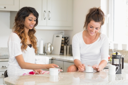 kitchen worktop: Two friends chatting over coffee at breakfast in kitchen Stock Photo