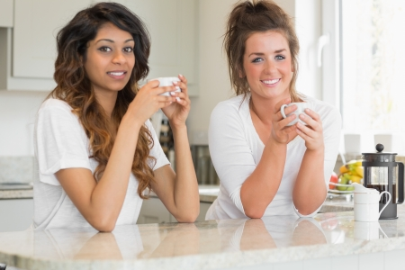 Two smiling women having coffee at breakfast in kitchen